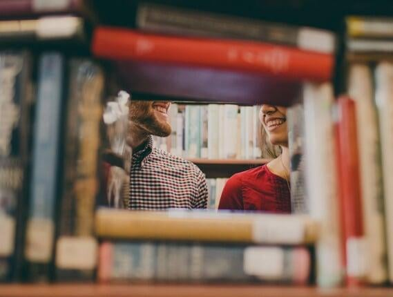 Man and woman standing behind a bookshelf and smiling at each other | Host Family Stay